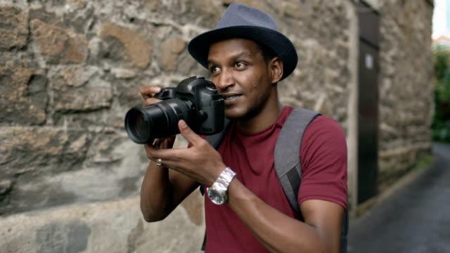 afrika mutlu turist alarak fotoğraf onun dslr fotoğraf makinesi. genç adam avrupa'da seyahat - fotoğraf teması stok videoları ve detay görüntü çekimi