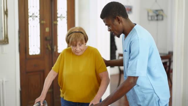 vidéos et rushes de travailleur de la santé africain aidant une femme âgée à marcher - infirmier