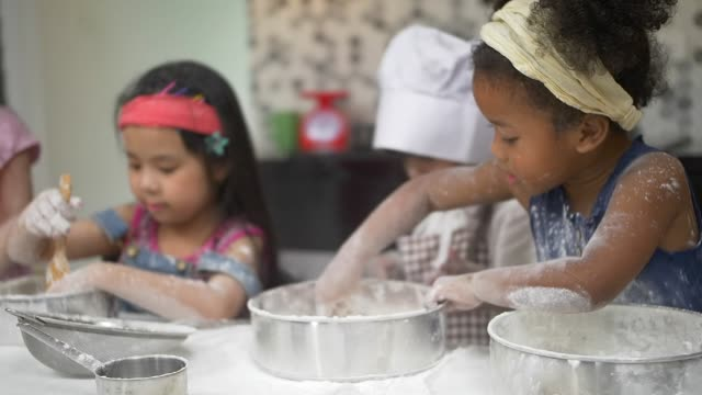 African Kid and friend clapping his hands filled with flour, playing with flour and baking together, Little bakers, happy family funny kids are preparing the dough, bake cookies in the home kitchen with slow motion video.
