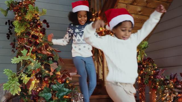 stockvideo's en b-roll-footage met afrikaanse jonge geitjes die onderaan de treden lopen om de giften van kerstmis te zien - christmas tree