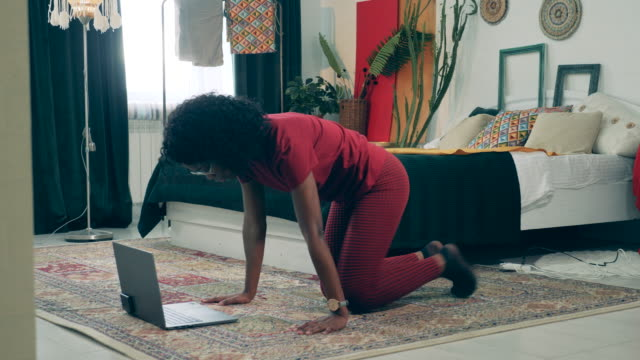vídeos de stock e filmes b-roll de african lady is doing exercises at home with her laptop. sport at home, fitness at home concept. - treino em casa