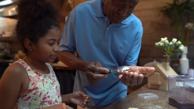 vídeos de stock, filmes e b-roll de avô de latino africano ensinando seu neto a cozinhar em casa - eles estão preparando o brigadeiro brasileiro - brigadeiro