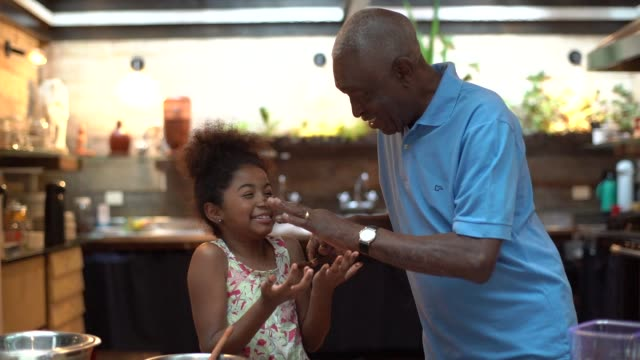 African latino grandfather teaching their grandchild how to cook at home - They are preparing Brazilian Brigadeiro