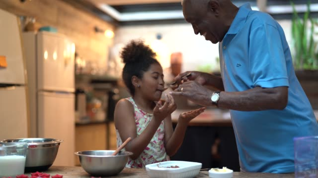 african latino grandfather teaching their grandchild how to cook at home - they are preparing brazilian brigadeiro - edificio residenziale video stock e b–roll