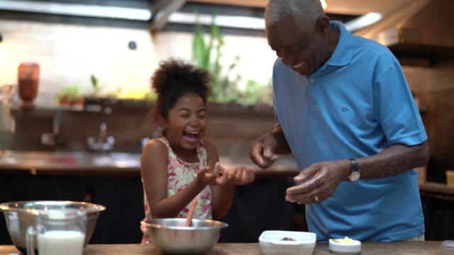 african latino grandfather teaching their grandchild how to cook at home - they are preparing brazilian brigadeiro - grandparents stock videos & royalty-free footage
