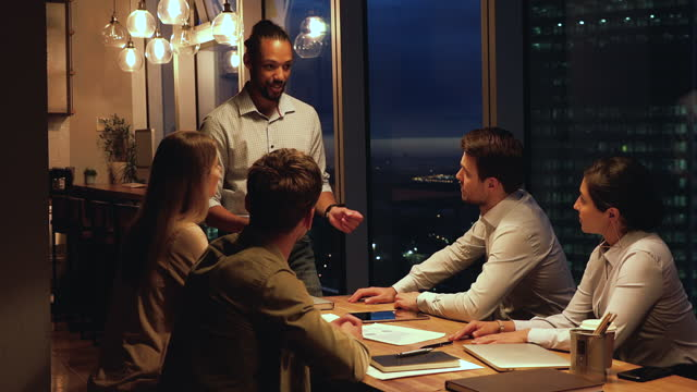 African leader brainstorm with team at night in office boardroom
