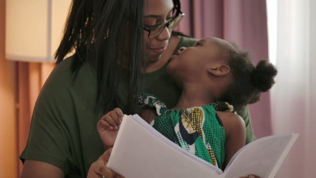 vídeos de stock e filmes b-roll de african little girl and her mother have a time together on bed at home. - afro