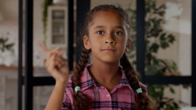 African little girl showing no, don't with finger Portrait of lovely elementary age african american girl showing no, don't, forbidden, warning with finger hand gesture, making reprimand or rebuke indoors, looking with determination. pigtails stock videos & royalty-free footage