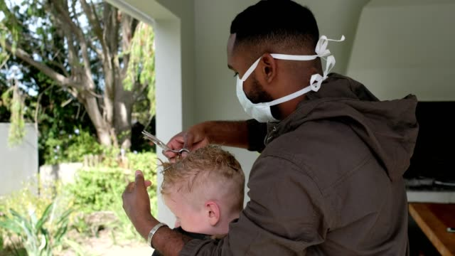 vídeos de stock e filmes b-roll de african male barber with face mask cutting a boys hair at home - covid hair