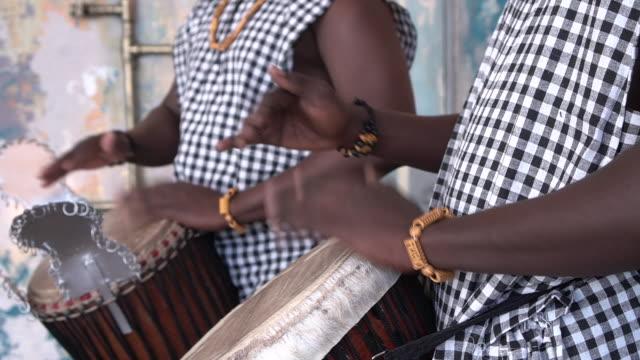 vídeos de stock, filmes e b-roll de mãos masculinas africanas tocando em tambor jembe, close-up - tradição