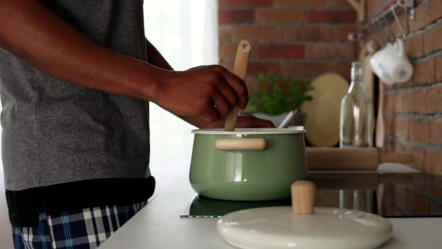 African man boiling water in pot standing in the kitchen, slow motion shot video