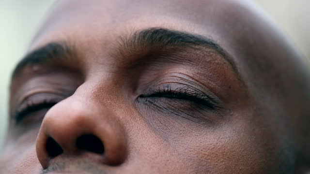 African man closing in meditation and contemplation, close-up black ethnicity eyes African man closing in meditation and contemplation, close-up black ethnicity eyes mindfulness stock videos & royalty-free footage