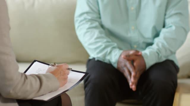 vidéos et rushes de homme africain ayant la consultation avec le psychologue - bloc note
