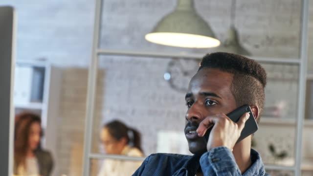 african man having phone conversation late in office - call center стоковые видео и кадры b-roll