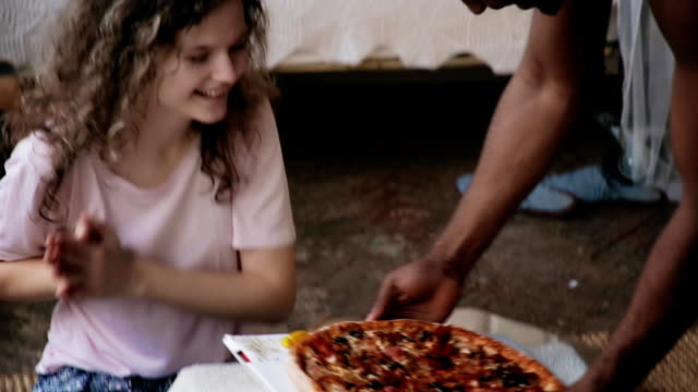 African man in pajamas brings pizza to hungry caucasian woman. Multiracial couple in pajamas smell the fast food video