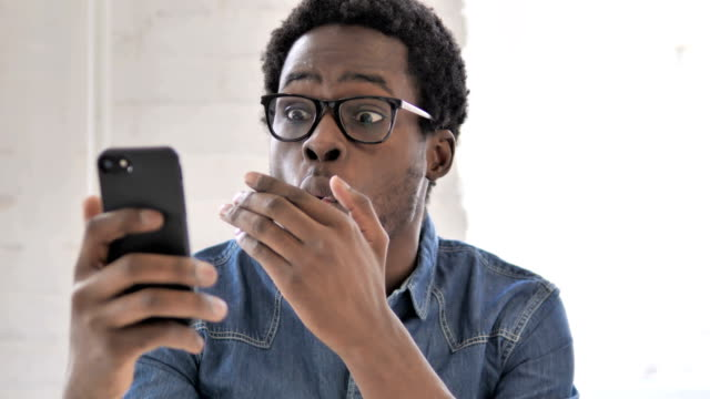 african man in shock while using smartphone - sorpresa video stock e b–roll