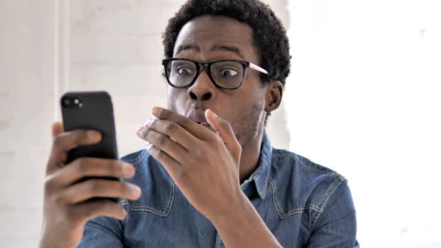 스마트 폰을 사용 하는 동안 충격에 아프리카 남자 - surprise 스톡 비디오 및 b-롤 화면