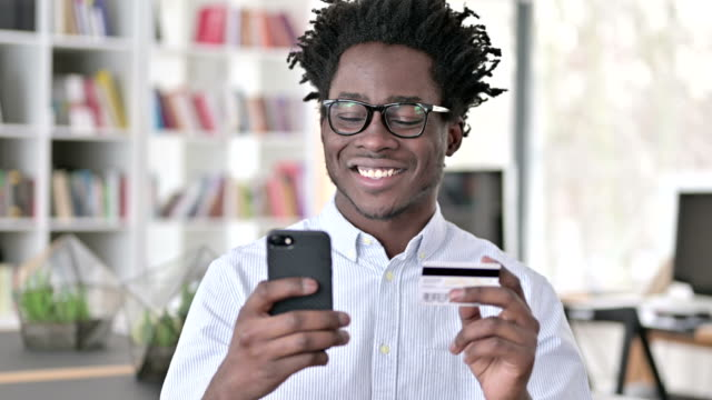 African Man making Credit Card Payment on Smartphone