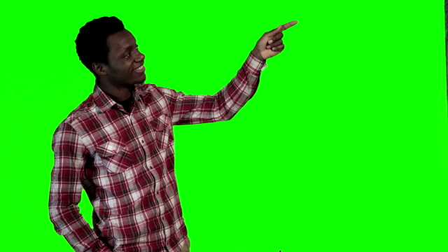 African man pointing on green