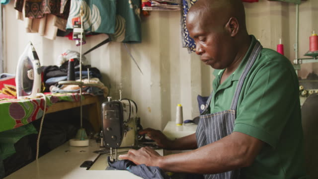 african man sewing tissue - tailor working video stock e b–roll