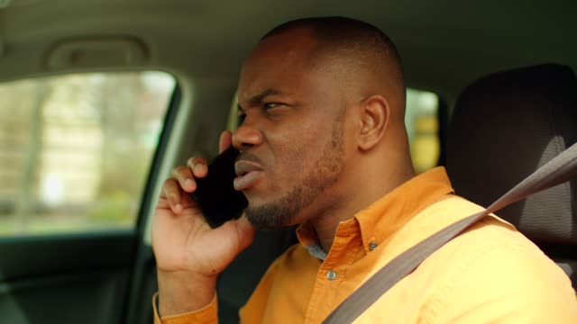 African man talking on cellphone while driving car