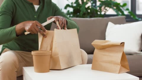 african man unpacking takeaway food at home consumption, eating and people concept - man unpacking takeaway food at home container stock videos & royalty-free footage