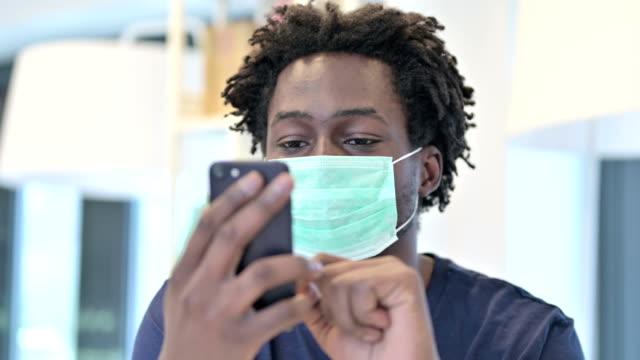 afrikanischer mann mit gesichtsmaske mit smartphone - smartphone mit corona app stock-videos und b-roll-filmmaterial