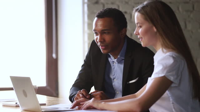Afrikanischer Manager macht Geschäftsangebot an kaukasischen Kunden mit Laptop – Video
