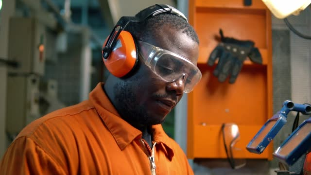 African marine engineer officer in engine control room ECR. African marine engineer officer in engine control room ECR. He works in workshop with equipment occupational safety and health stock videos & royalty-free footage