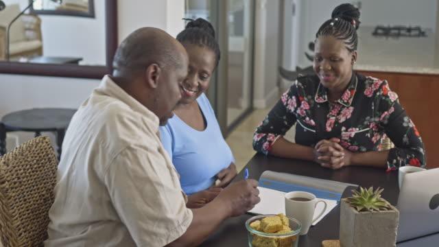 afrikanska mogna par undertecknar ett pensionering avtal med finansiella rådgivare hemma - försäkring bildbanksvideor och videomaterial från bakom kulisserna