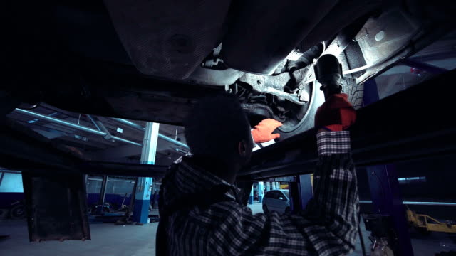 African mechanic working on the underside of a car video