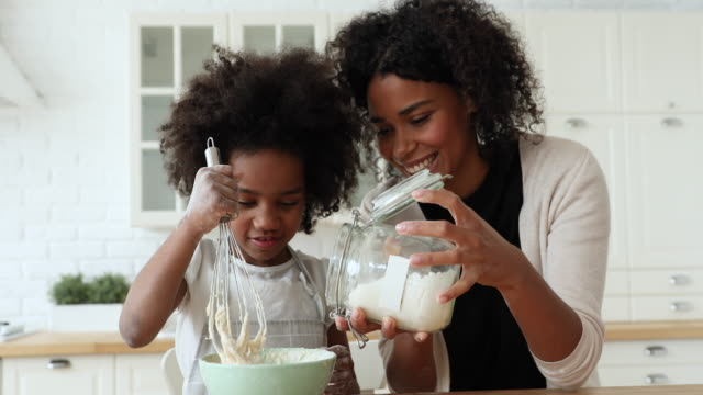 African mom and daughter making dough in bowl in kitchen African mom and small kid daughter cooking together making dough in bowl in kitchen. Happy mixed race family prepare cake mix ingredients for pie having fun baking pastry on holiday morning at home. baked stock videos & royalty-free footage