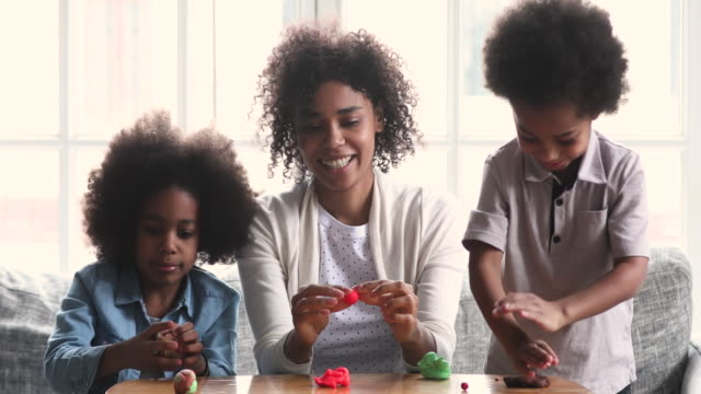 African mom teach two cute kids playing together sculpting playdough