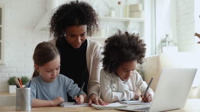 vídeos y material grabado en eventos de stock de madre africana, tutora ayudando a dos chicas de raza mixta estudiando juntas - cuidado infantil