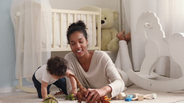 African mommy and cute baby daughter playing toys in bedroom