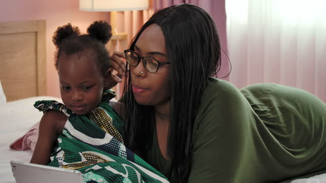 African mother and daughter spending time at home together.
