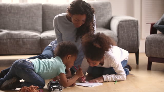 afrikansk mor och små barn sitter på varma golv ritning - golv bildbanksvideor och videomaterial från bakom kulisserna