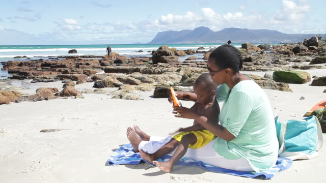 African mother and son at the beach, putting sunblock on African mother and son at the beach, putting sunblock on. Cape Town, South Africa indian ocean stock videos & royalty-free footage