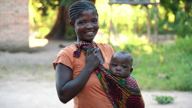 vídeos y material grabado en eventos de stock de madre africana con hijo bebé en casa - aldea