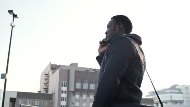 african office worker talking on phone outdoors - call center стоковые видео и кадры b-roll