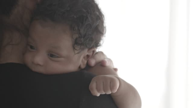 African or black boy sleeping on the shoulder ,mother take care him.slow motion footage.