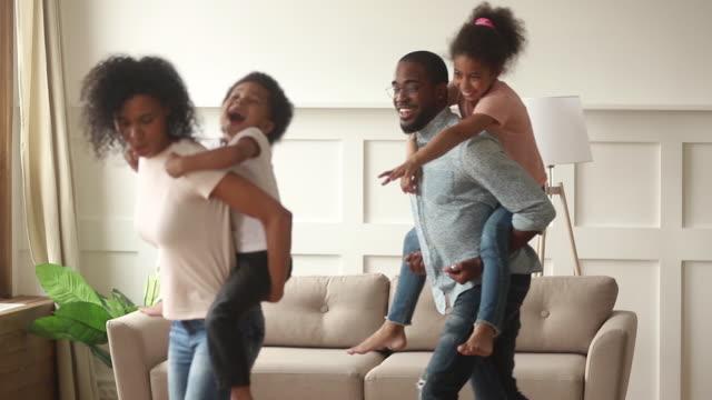 vídeos de stock, filmes e b-roll de pais africanos que carreg nos miúdos pequenos traseiros que têm o divertimento em casa - atividade