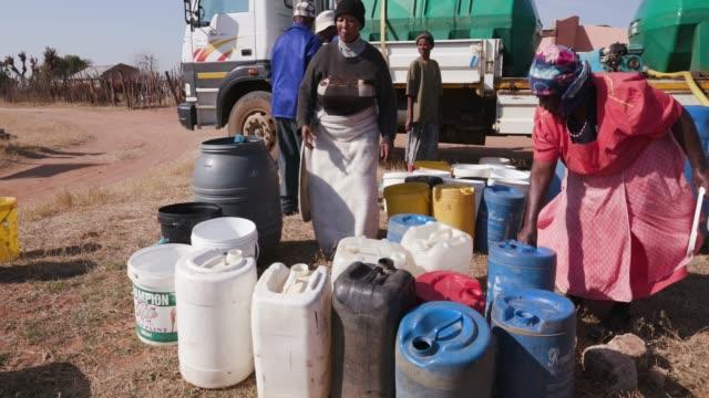 menschen in afrika sammeln wasser in behältern aus tankfahrzeugen wasser aufgrund der schweren dürre in südafrika - eimer stock-videos und b-roll-filmmaterial