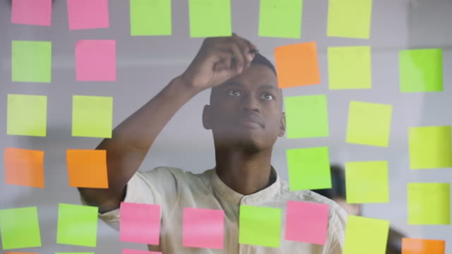african student worker writing replacing sticky notes on scrum board - post it video stock e b–roll