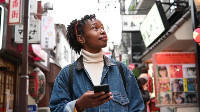 非洲遊客在日本使用應用程式在手機上和環顧四周 - 旅遊業 個影片檔及 b 捲影像