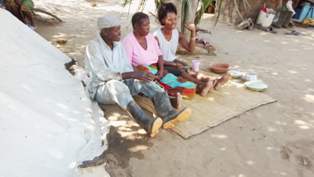 African Village Family having a Casual Banter While Seated Together Africa, Village, Woman, Lifestyle - African Farmer's Family Seated Together and having a casual conversation mortar and pestle stock videos & royalty-free footage