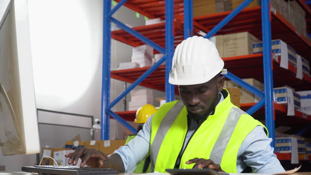 african warehouse manager sitting at desk using computer check inventory items online at distribution warehouse. black man worker  in Hard Hat typing keyboard entering data document  in workplace