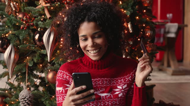 African woman buying online using smartphone and card on Christmas