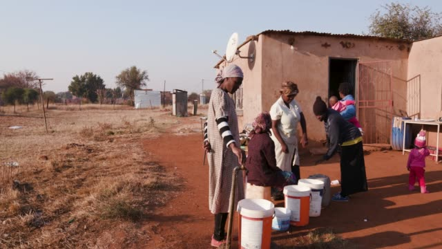 african woman collecting water from a tap in palstic buckets, while others stand in line and wait their turn - голодный стоковые видео и кадры b-roll