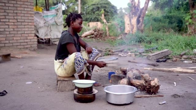 african woman cooking food in rural village, malawi, africa - голодный стоковые видео и кадры b-roll